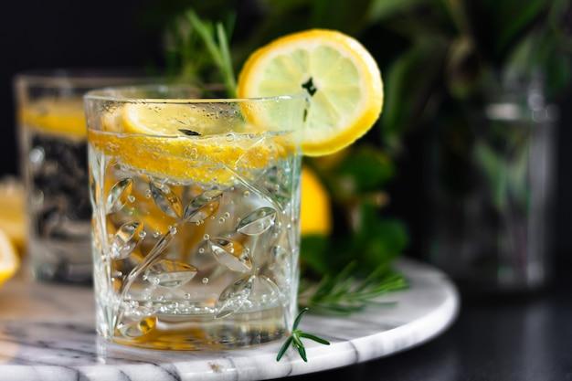 Bebida de verão em copos com rodelas de limão na bandeja de mármore.