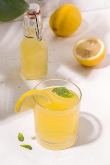 Bebida de verão, limonada de kombuchá fermentada ao lado de um limão. foto vertical