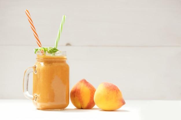 Bebida de verão saudável, batido de pêssego fresco misturado na mesa de madeira branca