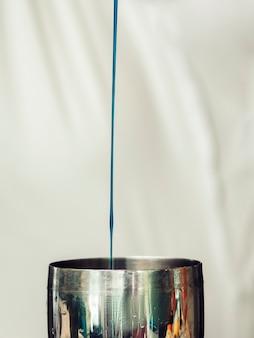Bebida derramada no shaker em fundo claro