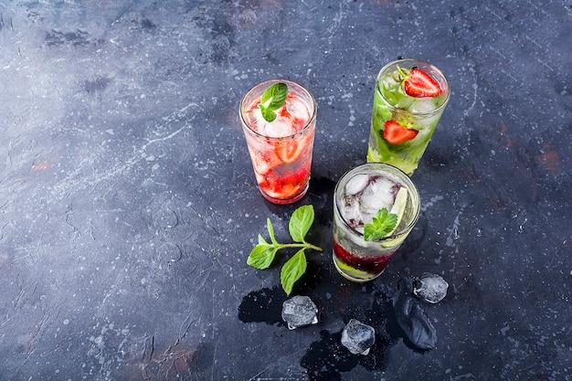 Bebida desintoxicante com morango, limão, cereja e hortelã na vista superior do fundo escuro