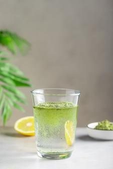 Bebida desintoxicante saudável com pó de superalimento verde em vidro