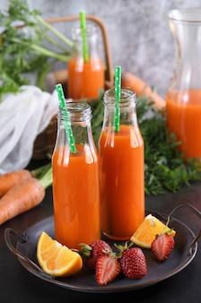 Bebida desintoxicante. suco de laranja com morango e cenoura feito na hora. para quem monitora sua saúde