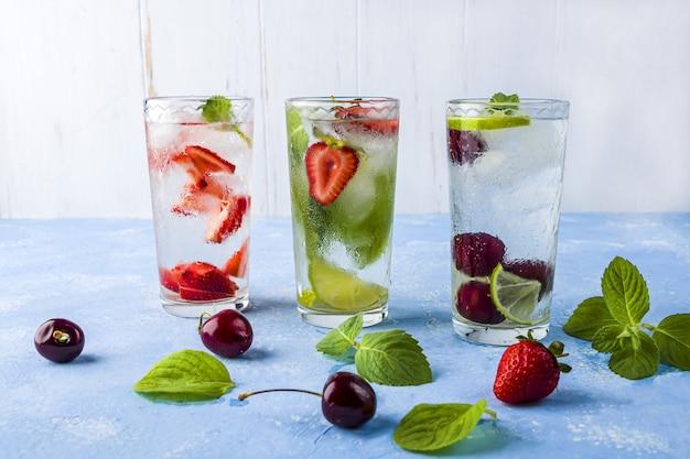Bebida detox com morango, limão, cereja e hortelã em uma mesa azul