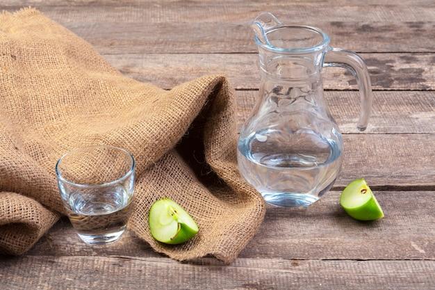 Bebida dietética de desintoxicação com fatias de maçã em água limpa e uma maçã fresca em uma mesa de madeira, close-up