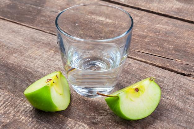 Bebida dietética de desintoxicação com fatias de maçã em água limpa e uma maçã fresca em uma mesa de madeira