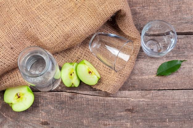 Bebida dietética de desintoxicação com fatias de maçã em água limpa e uma maçã fresca na mesa de madeira