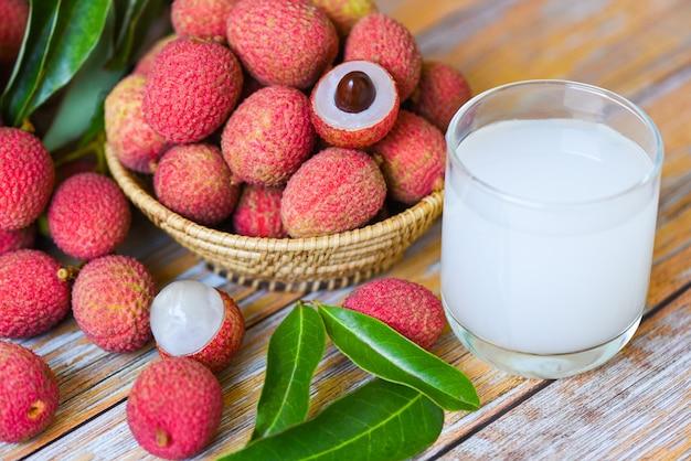 Bebida e fatia de lichia fresca descascadas com folhas verdes colhem na cesta do verão de frutas tropicais de árvore na tailândia - suco de lichia na mesa de madeira