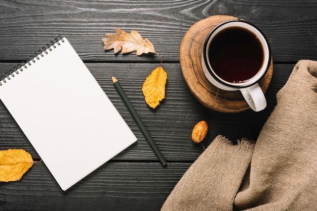 Bebida e pano perto de folhas e artigos de papelaria