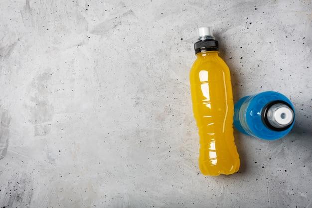 Bebida energética isotônica. garrafas com líquido transparente azul e amarelo