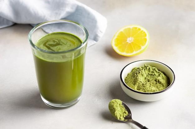 Bebida energética saudável e superalimento verde em pó em uma tigela na mesa