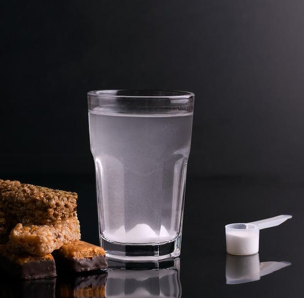 Bebida esportiva fortificada em um copo em um fundo preto