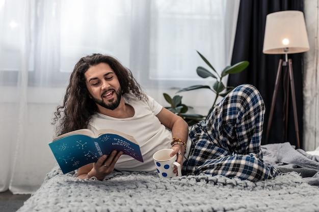 Bebida favorita. homem alegre e positivo deitado na cama com uma xícara de café enquanto lê um livro