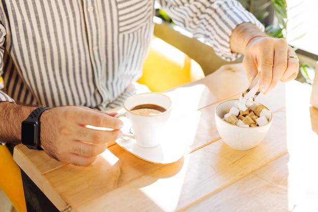 Bebida favorita. vista superior de uma xícara de café delicioso com um pouco de açúcar sendo colocado
