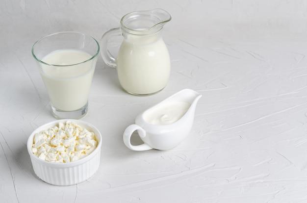 Bebida fermentada caseira em um copo de kefir, queijo cottage, creme de leite numa superfície branca