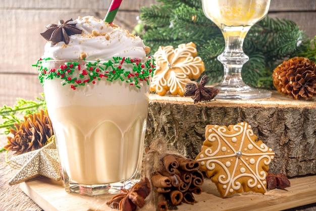 Bebida festiva de natal, coquetel de milkshake de gemada com sorvete, chantilly, granulado de açúcar colorido, fundo tradicional de madeira com decoração de natal e biscoitos de gengibre, copie o espaço