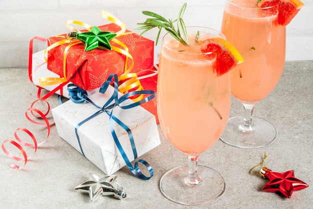Bebida festiva para festa de natal, coquetel de mimosa com champanhe, toranja e alecrim, em conto de pedra,