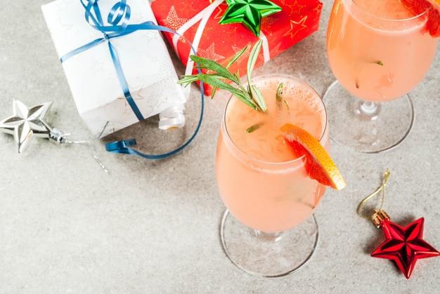Bebida festiva para festa de natal mimosa coquetel com toranja champanhe e alecrim em conto de pedra