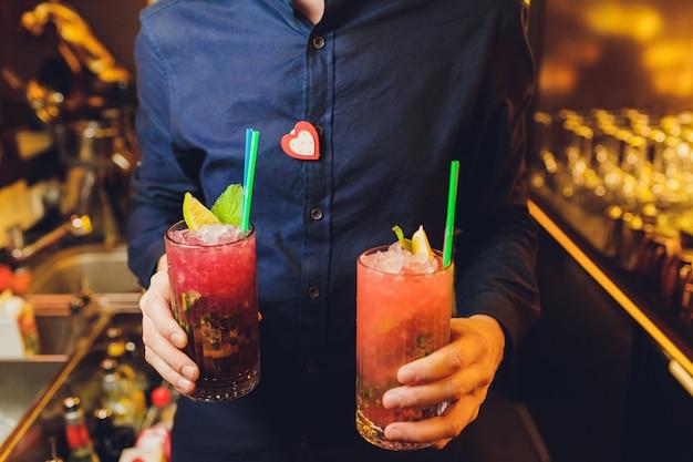 Bebida fresca cocktail nas mãos de um garçom.