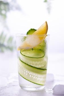 Bebida fresca, coquetel de gin tônico com pepino, limão e gelo na parede branca. na parede branca