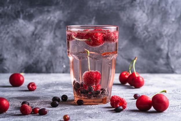 Bebida fresca de água com gás com bagas de cereja, framboesa e groselha em vidro facetado vermelho