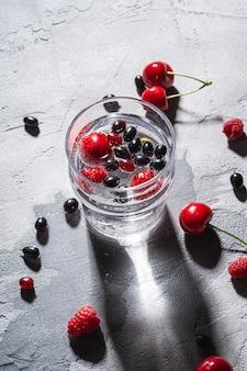 Bebida fresca de água gaseificada gelada com bagas de cereja, framboesa e groselha em vidro transparente sobre pedra
