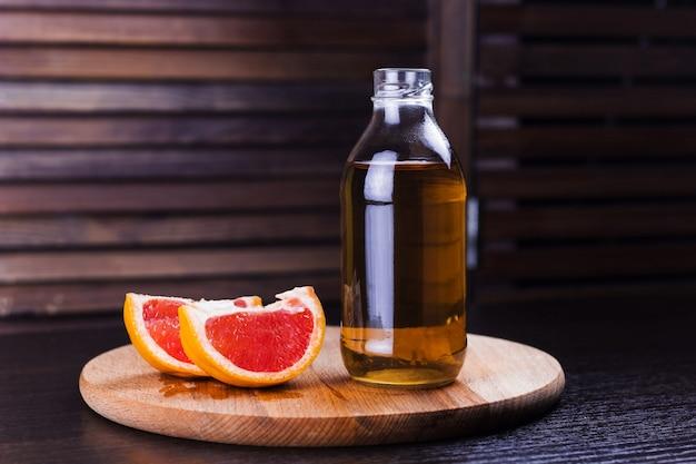 Bebida fresca de toranja em um fundo de madeira garrafa de vidro