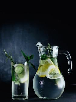 Bebida fresca de verão. água com gás desintoxicação de vidro saudável com limão, hortelã, alecrim e pepino em frasco de vidro sobre fundo escuro. conceito de comida saudável. dieta detox.