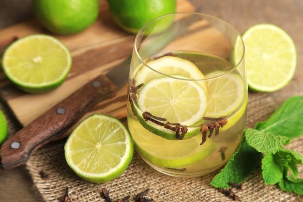 Bebida fresca de verão com limão e cravo em vidro, em superfície de madeira colorida
