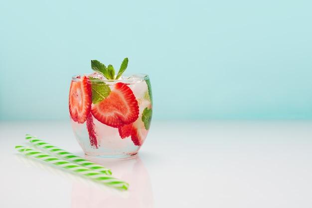 Bebida fresca de verão com morangos e hortelã em um azul