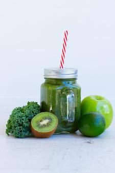 Bebida fresca e smoothy verde em potes de vidro com ingredientes