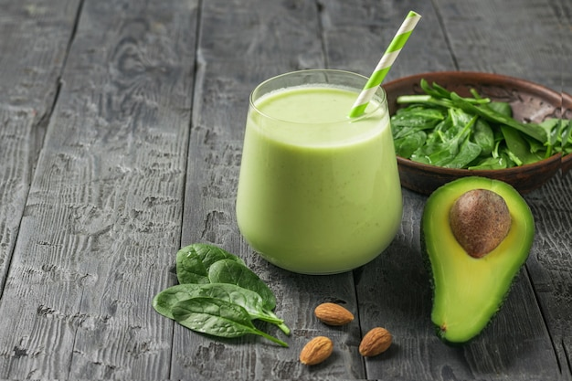Bebida fresca, folhas de espinafre e meio abacate em uma mesa rústica. produto de fitness. nutrição esportiva dietética.