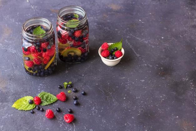 Bebida fresca fresca de desintoxicação com framboesas, mirtilos e kiwi em caneca de vidro. limonada em um copo com uma hortelã. o conceito de nutrição adequada e alimentação saudável. dieta de fitness. copie o espaço para tex