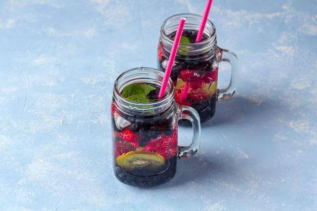 Bebida fresca fresca de desintoxicação com framboesas, mirtilos e kiwi em caneca de vidro. limonada em um copo com uma hortelã. o conceito de nutrição adequada e alimentação saudável. dieta fitness