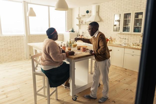 Bebida fresca. homem afro-americano simpático a derramar sumo no copo enquanto se preocupa com a mulher