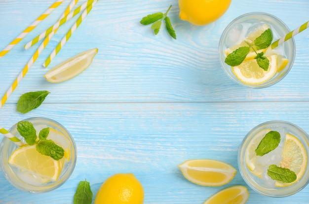 Bebida fria de verão refrescante com limão e hortelã na luz azul de fundo de madeira