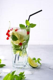 Bebida fria de verão, sangria, limonada ou mojito com limão fresco de groselha, folhas de hortelã limão com ingredientes.
