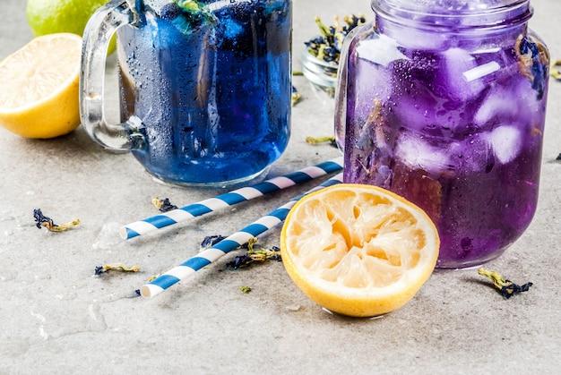 Bebida fria de verão saudável, chá de flor de ervilha de borboleta azul e violeta orgânica gelada com limas e limões