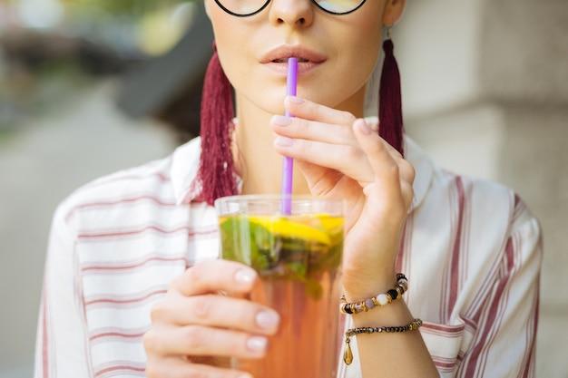 Bebida gelada. calma jovem tocando um canudo com os lábios enquanto bebe uma limonada gelada