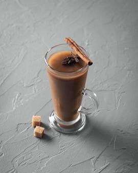 Bebida gelada com café e leite em copo com canela no fundo cinza da mesa, vertical