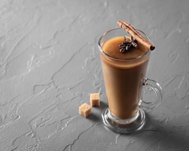 Bebida gelada com café e leite em copo com canela no fundo da mesa cinza, vista superior