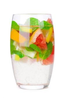 Bebida gelada com diferentes frutas cítricas e ervas em copos em um branco. coquetel