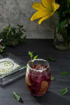 Bebida gelada com gelo e rodelas de limão em uma mesa cinza e um vaso com flores amarelas