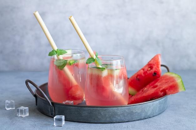 Bebida gelada de verão com melancia, folhas de hortelã e gelo em uma bandeja vintage. dois copos com canudos ecológicos de bambu