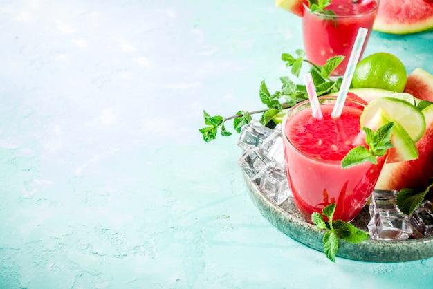 Bebida gelada de verão frutado, suco de melancia caseiro ou batido servido com limão e folhas de hortelã fresca, luz azul na moda fundo cópia espaço