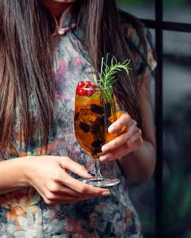 Bebida gelada em um copo com frutas nas mãos de uma menina
