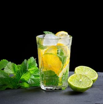 Bebida gelada feita a partir de pedaços de limão, limão e folhas de hortelã verde em um copo com gotas de água