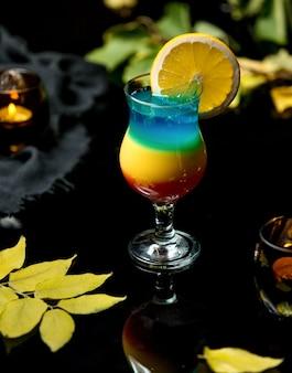 Bebida gelada multicolorida com uma fatia de laranja