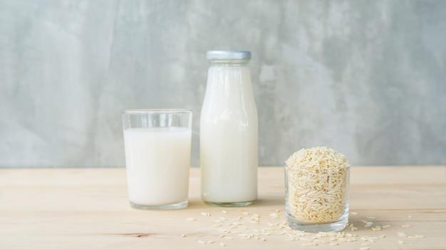 Bebida germinada do arroz integral e arroz integral em uma tabela de madeira.