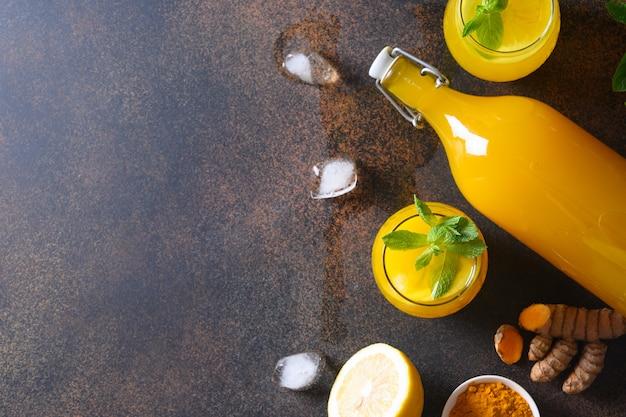 Bebida herbal indonésia de jamu com ingredientes naturais açafrão, gengibre no fundo marrom. espaço para texto.